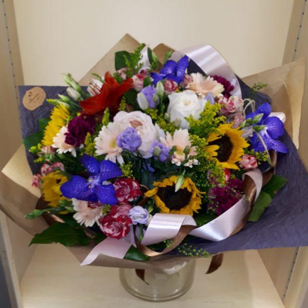 Букет из подсолнуха, ванды, кустовых роз, эустомы, гвоздик, ранункулюсов, герберы, роз, зелени