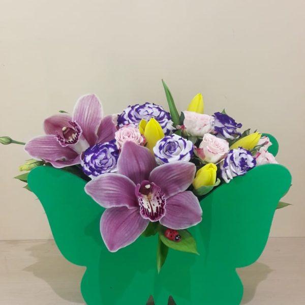 Букет из деревянной бабочки состоящий из орхидеи, кустовой розы, эустомы, тюльпанов, зелени