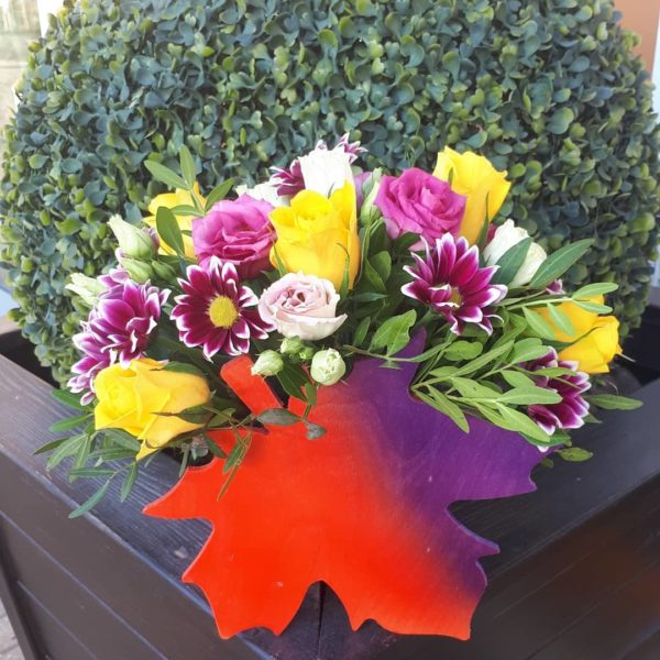 Букет в деревянном кленовом листе состоящий из роз, эустомы, хризантем, зелени