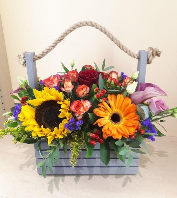 Букет в деревянном ящичке состоящий из Подсолнух, гербера, каллы, кустовой розы, одноголовой розы, гиперикума, эустомы, статицы